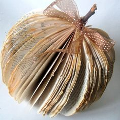 Nice pumpkin made of old book :-)Take the cover off an old book, cut pages into a curve, bend back and attach together and add stick and bow! Easy primitive fall pumpkin!