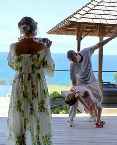 Blue Ivy, Mom Beyoncé and Dad Jay Z by the ocean in Italy as Dad balances Blue Ivy at n his arm.