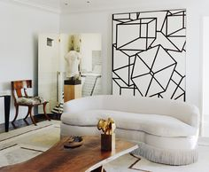Such a deft mix of modern and classic...the fur upholstery on the chair, kidney sofa with sexy fringe, organic live edge table, wonderful art and sculpture.  Really a masterful mix.