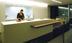 GF Concepts - Uw Interieurspecialist - het keukenblok wordt doorsneden door een houten blad - met de vlakke kastenwand een grootse keuken