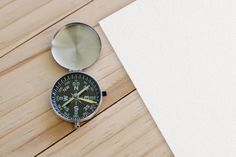 compass and paper on wooden table