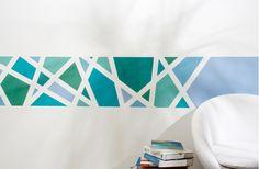 """Zugegeben, wir haben alle Register gezogen bei unserem Wandbild, um zu testen, ob das Klebeband """"Frogtape"""" hält, was es verspricht. Denn bei dem expressiven Muster gibt es mehrere Überschneidungspunkte des Klebebandes. Damit die geometrischen Felder in unterschiedlichen Grün- und Blautönen gut zur Wirkung kommen, bedarf es scharfer Kanten. Das heißt, Farbe darf nicht verlaufen. Aber was hat dieses Klebeband, was andere nicht haben?"""