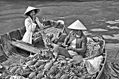 Selling Pineapples at the floating markets somewhere in the Mekong Delta. On location for Chefs Run Wild