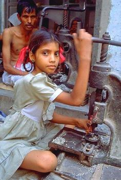 """This young Indian girl working in a glass factory is just one of India's many invisible child labourers. Girls who work from home tend to be the most """"invisible"""". Unlike boys, girls often do household chores in addition to fieldwork and often miss out on schooling. Around 60 per cent of India's girls over eight-years-old are unable to read or write."""