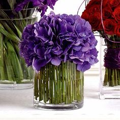 Small green bamboo reeds tied together with wire line the inside of the vase with purple hydrangea spilling out the top
