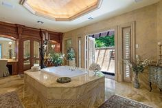 A luxurious soaking tub with a marble surround is the ultimate place to relax and unwind in this master bathroom. Shutter-style doors open up to a private garden, adding to the appeal of this elegant space. Beautifully carved his and hers vanities feature a mirrored storage closet to separate the spaces, and a tray ceiling above the bathtub completes the design.