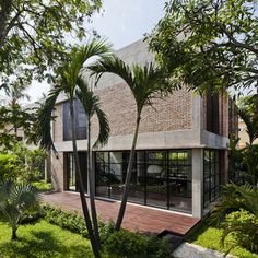 MM++ Architects replaces the old walls of a Vietnam house with red bricks and pivoting glass.