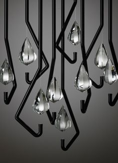 """Thomas Feichtner. """"One Crystal Chandelier"""" for Lobmeyr. There is a LED at the end of each of the black metal tubes."""
