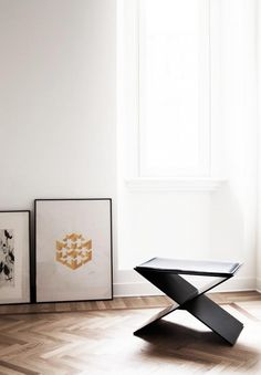 Living space with wood floors, art propped on the floor, and a modern stool