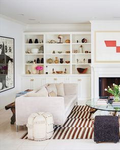 Striped rug, fiddle leaf fig, fireplace and built-in bookcases at Kelly Sawyer Patricof's Malibu Beach Cottage