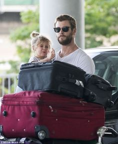 Daddy duties: As the couple wheeled their luggage out of the airport their daughter appear...