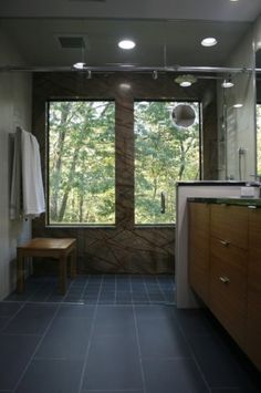 A smaller bathroom with an unenclosed, curbless shower requires that the entire floor be pitched toward the drain in the shower. Done properly, a bathroom such as this will drain itself dry shortly after it's used.