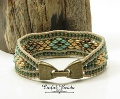 The center strip of this leather cuff has been beaded onto 1.5mm natural leather in a floral design using SuperDuos in bronze, stone green, and metallic flax. This strip is flanked on each side with Miyuki matte khaki iris seed beads. The clasp is an antique bronze fold over