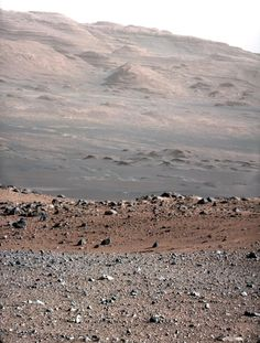 """Mount Sharp. Curiosity took this picture of her destination. It may just look like lots of rocks to you, but this is a scientific treasure trove. The different colors, sizes and shapes of rocks, etc. will tell a fascinating story to geologists. ©Mona Evans, """"Mars Facts for Kids"""" http://www.bellaonline.com/articles/art36393.asp"""