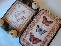 Butterfly Art featured on the top and inside of the of this upcycled Altoid Mint tin. On the bottom is vintage botanical art and four feet made with wood beads.Lacy-looking art paper has also been decoupaged to the sides.    A whimsical little box to store your keys, tea bag, small treasures, stamps, coins, jewelry, stash of chocolate, etc. or use as a fabulous little gift box.    Perfect also for enclosing a gift card!    The tin measures 3 3/4 X 2 1/4 X 3/4.