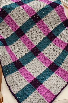 A tartan style granny square blanket in silver, magenta, petrol and emperor shades of Stylecraft Special DK.