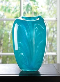 Who needs flowers when you have a vase this gorgeous? The unique flow of turquoise hue in this glass vase makes it a show-stopping accent for your mantel, and the uneven opening at top adds a touch of