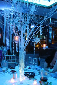 Winter Wonderland with white branches,twinkling hanging candles, snowflakes, crystals and icicles.