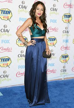 Pretty Little Liars actress Janel Parrish wore a blue bralet top and sapphire maxi skirt with XIV Karats jewelry to the 2014 Teen Choice Awards.