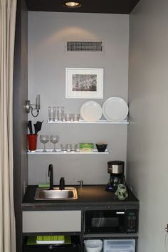 galley with refrigerator, sink, toaster oven, small electric skillet, microwave, dishes, flatware, utensils.