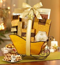 Festive Gold Holiday Sleigh Gift Basket - Gold Sleigh. Introducing our party in a sleigh! For the savory lover, there's honey wheat braided pretzels (delicious with the sweet and spicy mustard dip), smoky mozzarella mini baguettes, and peanut butter barrels. Craving sweet? Discover decadence like Fannie May cookies and cream bark, caramel filled caramel medallions, toffee, and a selection of cookies and wafer rolls. Reindeer sold separately! Gold Metallic Sleigh with Black Runners Honey…
