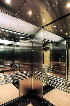 This Highly Polished Elevator Interior Hosts Triple Mirrored Stainless Steel Handrails on All Non-Access Walls.