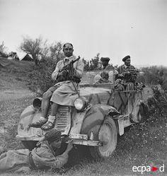 Lors de la campagne de Tunisie, au moment de la bataille du massif de l'Ousselat, des soldats du GTM (groupe de tabors marocains), qui combattent au sein de la DMM (division de marche du Maroc), montent en ligne et, le temps d'une photographie, posent juchés sur un véhicule. Ils ont participé à la récupération d'un important matériel ennemi : le soldat assis sur le capot est armé d'un MP 40 pris à l'armée allemande, la voiture est une voiture de liaison Fiat 508 CM prise aux Italiens. Date…