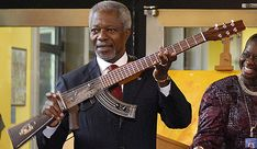 Former UN Secretary-General Kofi Annan shows an AK-47 assault rifle that has been transformed into an electric guitar.