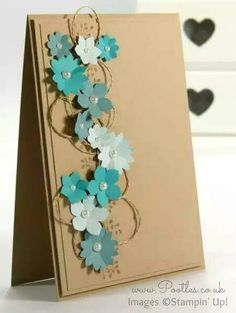 handmade greeting  card ... layers of kraft panels ... column of punched flowers in aquas on looped gold threads and tone on tone stamped branches of buds ...
