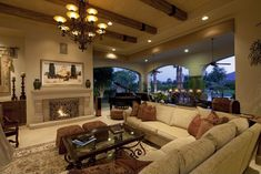Luxurious living room fully open to an immense patio space at right, stands large beige sectional beneath a soaring ceiling with exposed wood beams and a wrought iron chandelier. Shades of brown punctuate the tone, with dark wood and glass coffee table sitting before fireplace at center.