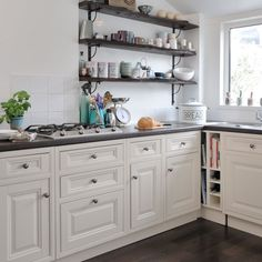 Small kitchen with white cabinetry, black worktops and open shelving and