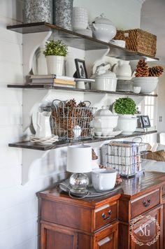 Open shelving layered with white pieces and accented with colors and textures.