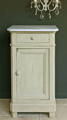 A French side table painted in Versailles against a wall painted in Graphite.  Soft delicate lightly yellowed dusky green that is sophisticated and gentle yet it works well with modern pieces too.