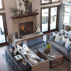 LOve: mesita para el café (baúl), forma y tono del sofá, combinación de tonos (beige, dark wood, gray/blue), Iluminación, concepto high ceiling. Like: Cuadro de caballos, mueble de madera oscura y cojines.