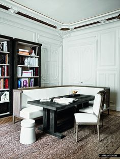 a mix of classic with contemporary bookshelves & furnishings, herringbone wood floors , Parisian Apartment of Gilles & Boissier, white walls accent the original period details