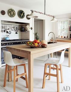 The kitchen's light fixture, table, counter, and tile backsplash were designed by Cotton | archdigest.com