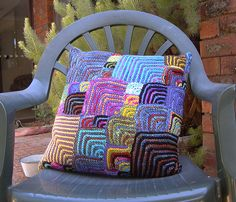 Knitted Cushion I knitted heaps of little mitred squares and finally sewed them all together into a very multicoloured cushion! It's a very comfy cushion too. :-) Blogged here - randomapplique.blogspot.com/2007/02/another-cushion.html