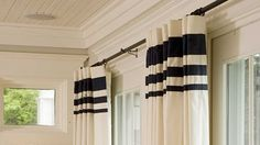 Wide bands of fabric at the headings of these draperies turn ready-made into a bolder statement. Get this look for your home by purchasing inexpensive solid curtain
