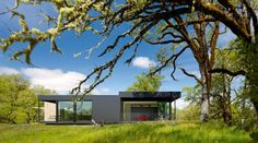 """Residential Architecture: Burton Residence by Marmol Radziner: """"..This vacation home is set on the crest of a grassy knoll on a 160-acre site in Mendocino County, California, USA. The goal was to preserve and enhance the natural beauty of the property by siting the retreat in a careful, simple, and unobtrusive manner. The 10-module home forms an L-shaped plan, framing views of a canopy of mature oak trees to the south and east..The road leading to the house climbs the hill and ends at the..."""