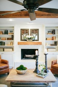 Painted white brick + large natural wood mantle . Love #fixerupper