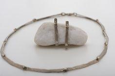 Gehamerd halssnoer in 18 kt wit goud naturel tint, met bijpassende oorbellen gezet met fijne diamantjes. Wim Meeussen