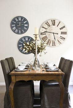 Dark-gray, slip-covered parsons chairs + clocks