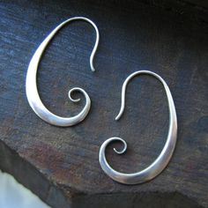 Simple, elegant, silver swirl hooked earrings by aprilkawaoka. $68.00, via Etsy.