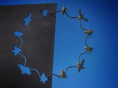 Sculpture of flying birds and cut-out birds on steel. Bing Dawe, Titipounamu – A Necklace With Lost Gems (Laser cut steel, bronze). Seen at Sculpture in the Gardens 2015/16, Auckland Botanic Gardens, New Zealand. Image: Su Leslie, 2016