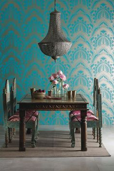 Intricate detailed peacock feather wallpaper design created in metallic gold on vivid turquoise.