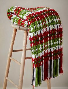 Get cozy this holiday season with this woven plaid blanket crocheted in festive shades of Caron United. (Yarnspirations)