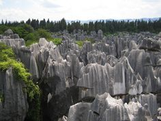 The place is called Stone Forest or Shilin. These rocks are a set of limestone formations located in Yunnan Province, China. The tall rocks are formed in such a way that it seems as if huge stalagmites have emerged from the ground, with many looking like petrified trees thereby creating the illusion of a forest made of stone. Since 2007, it has been under UNESCO World Heritage Sites. The site is classified as an AAAAA-class tourist site.    (Pic by flickr user maveric2003)