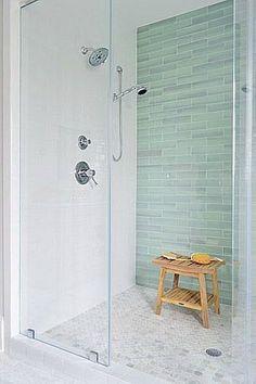focal shower wall. Nice shower system. Teak bench. Shampoo storage?: