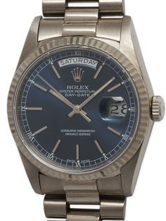Rolex Day Date President ref# 18239 18K WG circa 1998 - Rolex 18K WG Day Date President ref# 18239, K serial # circa 1998. Featuring a 36mm diameter case with fluted bezel, sapphire crystal, and very pleasing original sapphire blue dial with applied silver indexes and hands. Powered by calibre 3055 quick set date movement. With excellent condition tight original President bracelet with hidden clasp. Great looking watch! In excellent mechanical and cosmetic condition and offered with our 1…