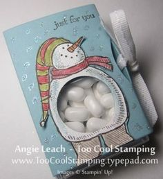 """Snow Much Fun Tic Tac Holder The base of the holder is created with a Two Tags die-cut tied up with a Whisper White Stitched Grosgrain Ribbon. I colored one of the snowman images from Snow Much Fun using Blender Pens and Ink Pads. After I cut out the colored image, I adhered it to the holder then punched out his tummy with the 1"""" Circle Punch."""